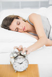 Attractive woman turning off the alarm clock lying on her bed