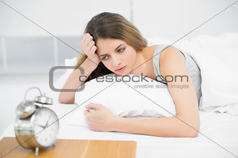 Calm attractive woman lying thoughtful on her bed