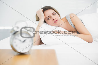 Tired brunette woman lying on her bed gazing
