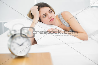 Cute young woman lying exhausted in her bed
