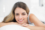 Beautiful brunette woman smiling at camera lying on her bed
