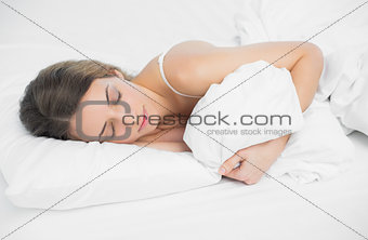 Sweet brunette woman sleeping holding her cover