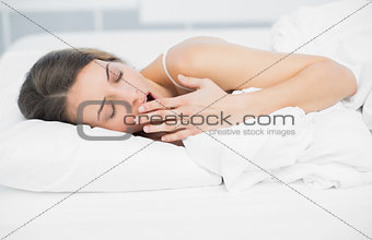 Tired attractive woman yawning while lying on her bed