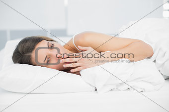 Beautiful yawning woman lying under the cover on her bed