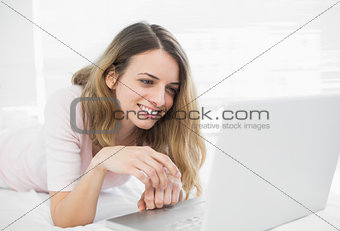 Attractive woman making smiling use of her notebook