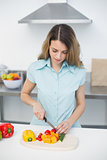 Concentrated young woman standing in kitchen cutting vegetables