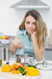 Young cute woman cooking while smiling at camera