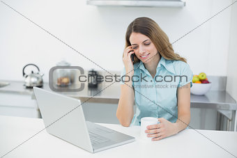 Amused gorgeous woman using her notebook while holding a cup