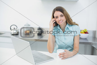 Attractive young woman posing in her kitchen smiling at camera