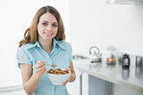 Content woman showing a bowl filled with cereals