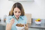 Happy brunette woman eating cereals standing in her kitchen