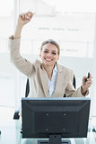 Content blonde businesswoman cheering sitting on her swivel chair