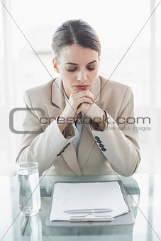 Focused young businesswoman sitting at her desk reading her notes