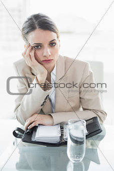 Attractive bored businesswoman looking at camera while sitting at her desk