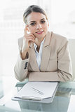 Thinking young businesswoman sitting at her desk