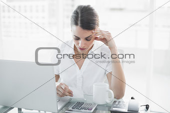 Attractive focused businesswoman working sitting at her desk