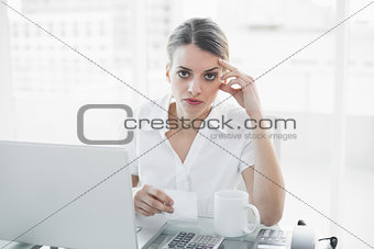 Unhappy businesswoman working sitting at her desk