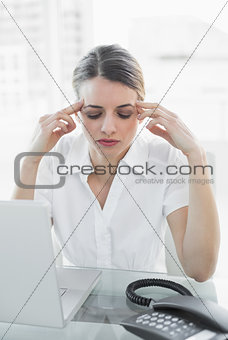 Beautiful suffering businesswoman having headache sitting at her desk