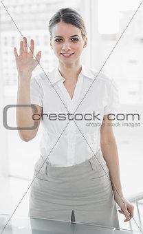 Beautiful businesswoman waving standing in her office