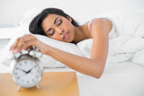 Lovely tired woman turning off the classic alarm clock