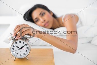 Attractive tired woman turning off the alarm clock