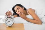 Lovely yawning woman turning off the retro alarm clock