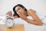 Cute yawning woman lying in her bed while turning off the alarm clock