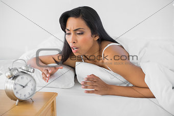 Attractive upset woman lying under the cover on her bed