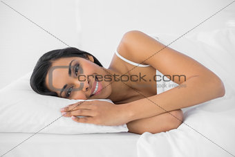 Calm smiling woman lying relaxing in her bed smiling at camera