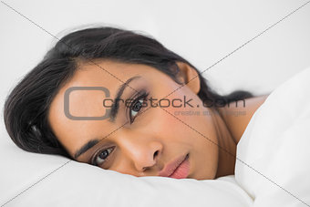 Attractive woman lying in her bed looking seriously at camera
