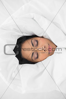 Beautiful woman sleeping lying under cover on her bed