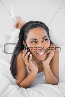 Cute woman phoning while lying on her bed