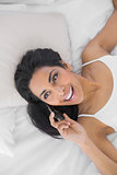 Cheerful smiling woman phoning lying on her bed