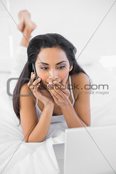 Astonished natural woman phoning while using her notebook