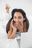 Natural surprised woman lying on bed phoning