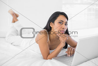 Cute woman using her notebook lying on bed