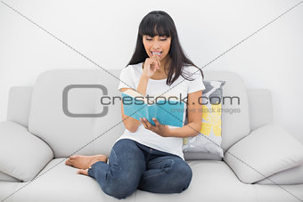 Calm dark haired woman reading a book sitting on couch