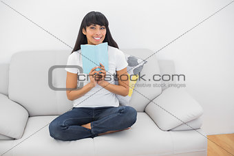 Attractive young woman holding a book smiling at camera