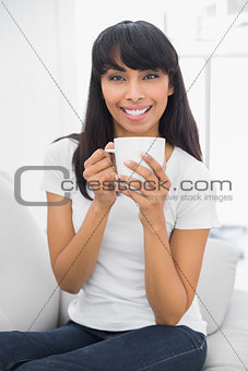 Calm beautiful woman holding a cup smiling at camera