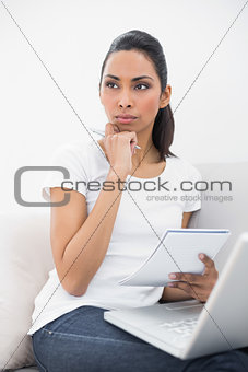 Cute thinking woman holding a notebook and laptop