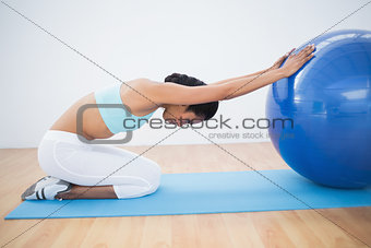 Fit woman stretching her body using a fitness ball