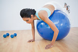 Cute sporty woman training on fitness ball