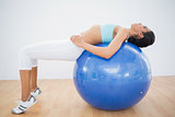 Concentrated toned woman training on fitness ball