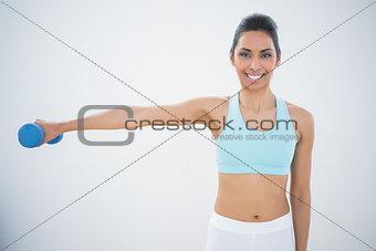 Slender dark haired woman lifting blue dumbbell