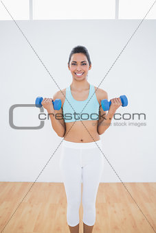 Beautiful slender woman lifting blue dumbbells
