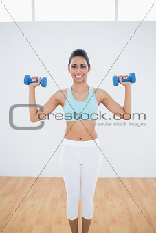Attractive slim woman lifting blue dumbbells