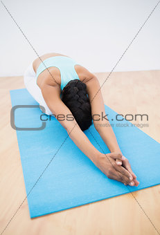 Slender dark-haired woman stretching on blue exercise mat