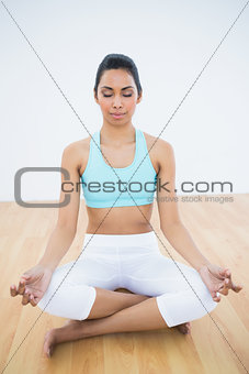 Peaceful slim woman meditating in lotus position