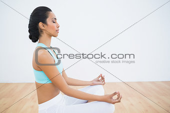 Attractive calm woman meditating sitting in lotus position