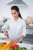 Beautiful calm woman standing in kitchen cutting vegetables